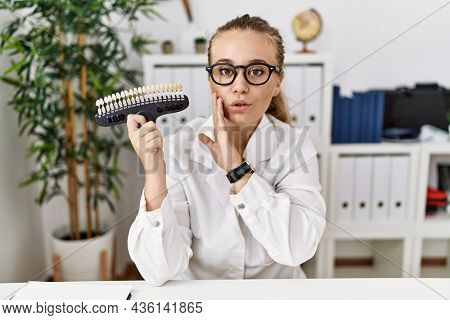Young caucasian woman holding teeth whitening palette hand on mouth telling secret rumor, whispering malicious talk conversation