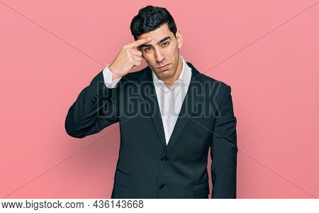 Handsome hispanic man wearing business clothes pointing unhappy to pimple on forehead, ugly infection of blackhead. acne and skin problem