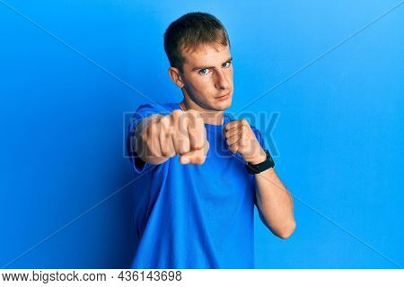 Young caucasian man wearing casual blue t shirt punching fist to fight, aggressive and angry attack, threat and violence