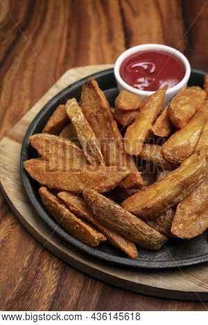 Spicy Curry Powder Coated Crispy Deep Fried Potato Wedges On Wood Table Background
