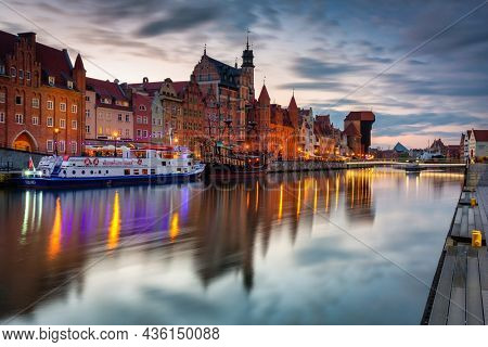 Gdansk, Poland - May 23, 2021: Architecture of the main town with historical port crane in Gdansk over Motlawa river at susnet, Poland.