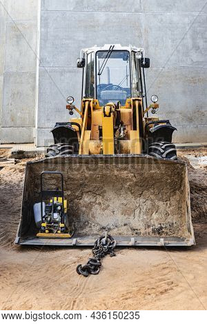 Heavy Front Loader On A Construction Site With A Construction Tool In The Bucket. Equipment For Eart