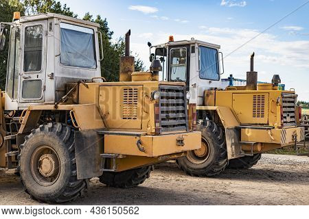 Two Heavy Wheel Loaders Are Standing At A Construction Site. Equipment For Earthworks, Transportatio