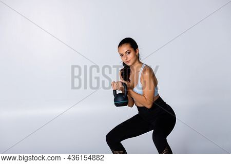 Fitness Woman Lifts Kettlebell With Both Arms As Exercise To Build Muscle, Fit Trainer Showing Weigh