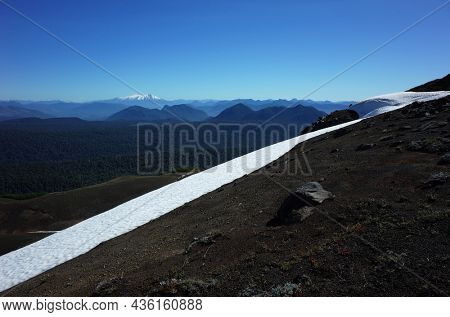 Diagonal snow line on mountain slope and view of mountains on horizon, Villarrica National Park, Chile, Nature of South America, Patagonia Andes landscape