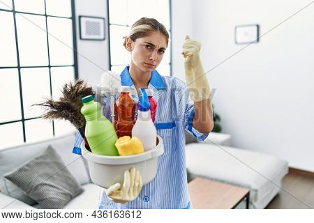 Young blonde woman wearing cleaner uniform holding cleaning products annoyed and frustrated shouting with anger, yelling crazy with anger and hand raised