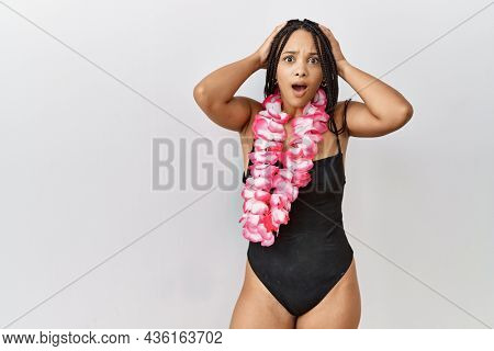 Young african american woman wearing swimsuit and hawaiian lei crazy and scared with hands on head, afraid and surprised of shock with open mouth