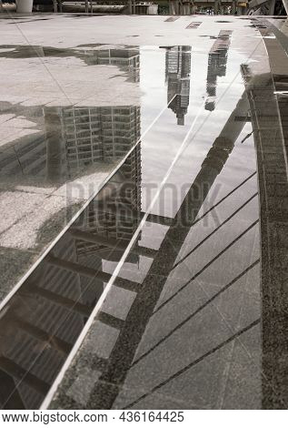 Photo Reflections Of Bridge Structure, Buildings And Sky Above A Puddle Of Rain Water On The Skywalk