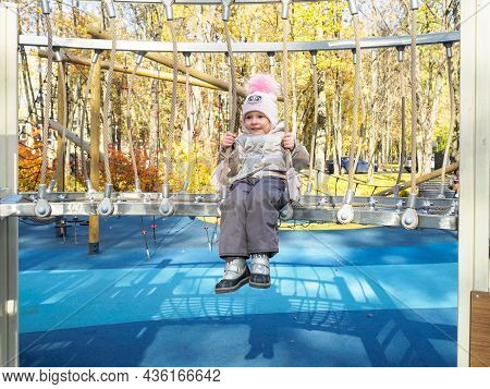 Little Girl Child On A Climbing Frame In The Playground. A Child Plays On The Playground On A Sunny