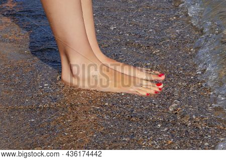 Female Feet On The Background Of Sea Sand In Summer.