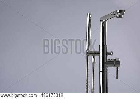 Modern Bathtub Faucet With Hand Shower On Grey Background. Space For Text