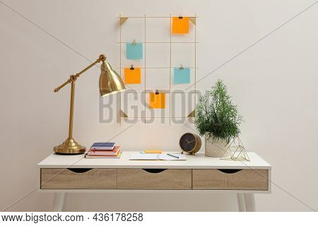Memo Board With Colorful Notes Hanging On White Wall Over Desk Indoors