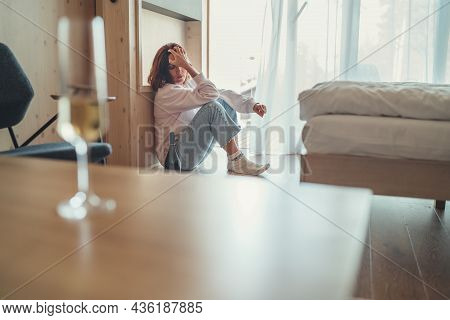 Sad Woman Sitting On The Floor Next To Window In The Bedroom With An Opened Bottle Of Alcohol. Unfoc