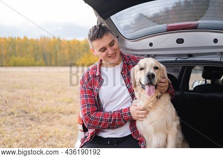 A Man Sits With His Dog In The Trunk Of A Car In The Autumn Forest. Traveling With A Pet. A Trip To