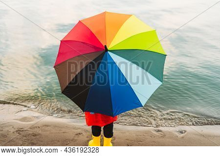 Boy In A Red Raincoat And Yellow Rubber Boots Holds Rainbow Umbrella Standing At Beach. Child With C