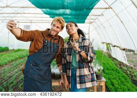 Happy middle aged multiethnic couple of farmers working in a greenhouse together taking a selfie with mobile phone