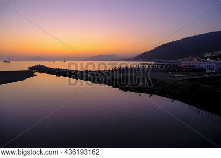 Beautiful Pink Sunset In Sea Across Boats, Mountains On The Horizon. Natural Background. Vacation At