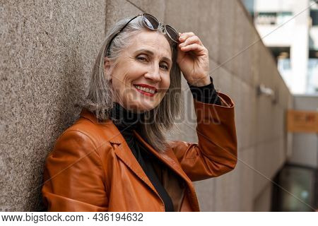 Grey senior woman in leather jacket smiling at camera while leaning on wall outdoors