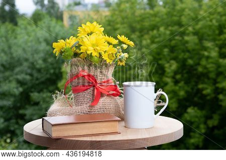 Summer Scene With Yellow Flowers, Book And White Coffee Cup With Steam On Wooden Table At Balcony. C