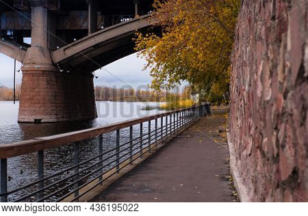 Sidewalk With Railings Along  River.  Large Stone Bridge With Arches Rises Above  Surface Of  Reserv
