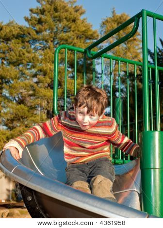Young Boy In Sweater On Playground Slide
