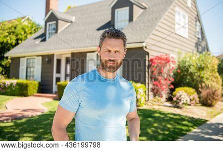 Unshaven Guy Standing Near New House, Realtor