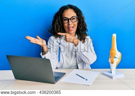 Beautiful middle age woman doctor at orthopedic clinic amazed and smiling to the camera while presenting with hand and pointing with finger.