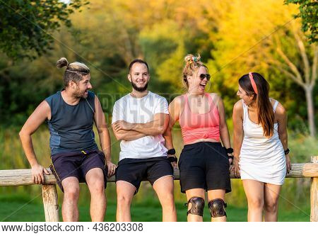 Group Of Friends Laughing While Resting In A Railing In A Park