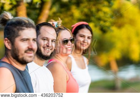 Selective Focus On A Man With Beard Standing With A Group Of Friends In A Park