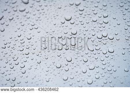 Raindrops On Glass Against Gray Sky Closeup