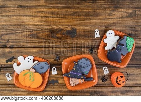 Halloween Gingerbread Cookies, Pumpkin, Tombstone, Witch Hat, Black Cat On Plates Over Wooden Table