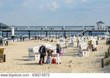 Heringsdorf, Germany - April 20, 2014: People Enjoy Pier And Beach Of Heringsdorf, Germany. The Balt