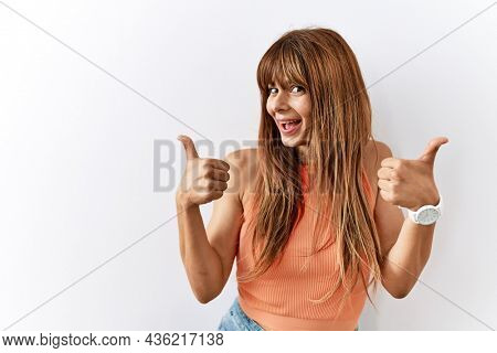 Hispanic woman with bang hairstyle standing over isolated background success sign doing positive gesture with hand, thumbs up smiling and happy. cheerful expression and winner gesture.
