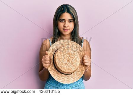 Young latin woman holding summer hat skeptic and nervous, frowning upset because of problem. negative person.