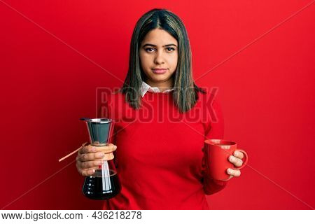 Young latin woman holding coffee filter and cup relaxed with serious expression on face. simple and natural looking at the camera.