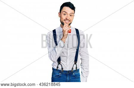 Hispanic man with beard wearing hipster look with bow tie and suspenders looking confident at the camera with smile with crossed arms and hand raised on chin. thinking positive.
