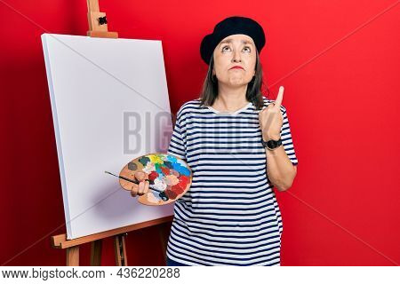 Middle age hispanic woman standing drawing with palette by painter easel stand pointing up looking sad and upset, indicating direction with fingers, unhappy and depressed.