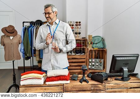 Middle age hispanic man working as manager at retail boutique disgusted expression, displeased and fearful doing disgust face because aversion reaction.