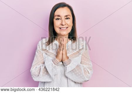 Middle age hispanic woman wearing casual clothes praying with hands together asking for forgiveness smiling confident.