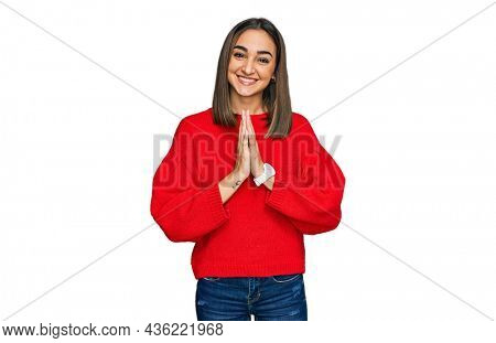 Beautiful brunette woman wearing casual winter sweater praying with hands together asking for forgiveness smiling confident.