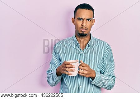 Young african american man drinking a cup of coffee in shock face, looking skeptical and sarcastic, surprised with open mouth