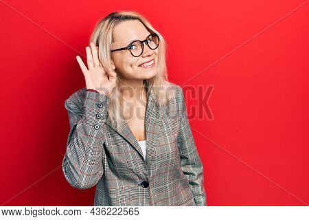 Beautiful caucasian blonde woman wearing business jacket and glasses smiling with hand over ear listening and hearing to rumor or gossip. deafness concept.