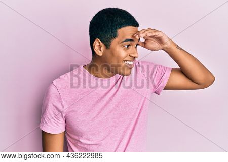 Young handsome hispanic man wearing casual pink t shirt very happy and smiling looking far away with hand over head. searching concept.