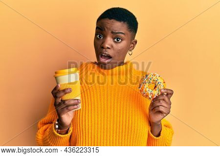 Young african american woman eating doughnut and drinking take away coffee in shock face, looking skeptical and sarcastic, surprised with open mouth
