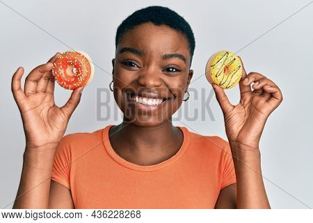 Young african american woman holding tasty colorful doughnuts on eyes winking looking at the camera with sexy expression, cheerful and happy face.
