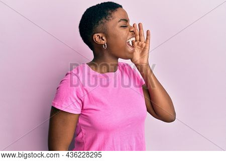 Young african american woman wearing casual pink t shirt shouting and screaming loud to side with hand on mouth. communication concept.