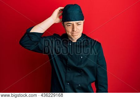 Handsome young man wearing professional cook uniform and hat confuse and wonder about question. uncertain with doubt, thinking with hand on head. pensive concept.