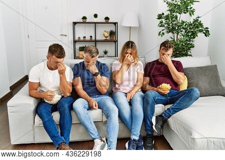 Group of middle age people sitting on the sofa at home tired rubbing nose and eyes feeling fatigue and headache. stress and frustration concept.