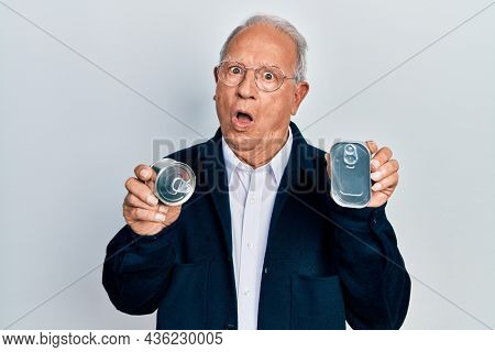 Senior man with grey hair holding canned food in shock face, looking skeptical and sarcastic, surprised with open mouth