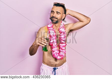 Young hispanic man wearing swimsuit and hawaiian lei drinking tropical cocktail smiling confident touching hair with hand up gesture, posing attractive and fashionable